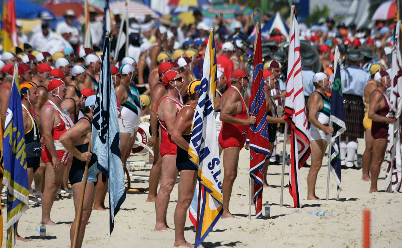 Surf lifesavers standing on the beach in their club costumes and holding their club flags. Australian Surf Life Saving Championships, Kurrawa, Queensland, 2006.