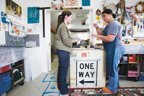 Museum curator Megan Parnell talks with artist Fatima Killeen in a studio. They stand either side of bench where a large 'ONE WAY' traffic sign is taped.