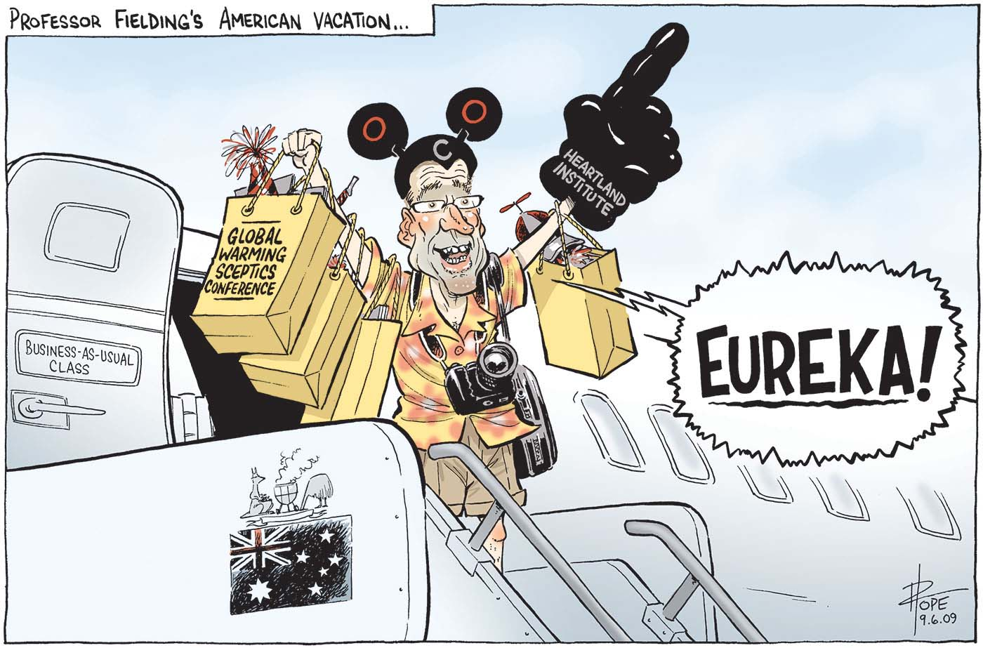 A colour cartoon titled 'Professor Fielding's American vacation ...'. Steve Fielding emerges from an aeroplane and stands at the top of the stairway, dressed as a tourist. He shouts 'Eureka!', carries 'Global Warming Sceptics Conference' showbags and wears Mickey Mouse style ears and an oversized 'Heartland Institute' foam hand. The plane door is labelled 'Business-as-usual' class and the Australian flag and coat of arms appears on the side of the stairs. The coat of arms shows the kangaroo standing beside a smoking kettle barbecue, its pouch full of what looks like coal, while the emu buries its head. - click to view larger image