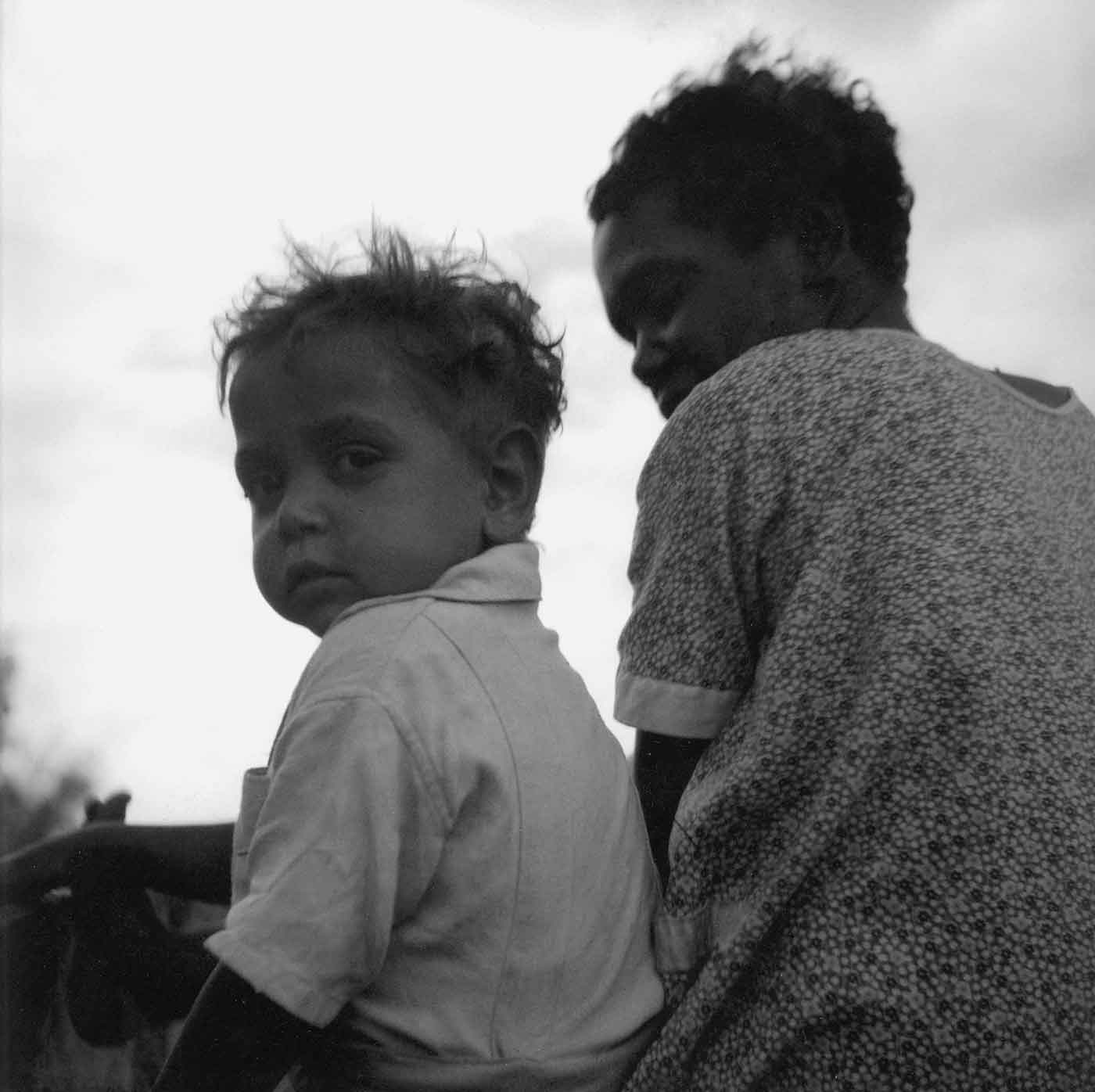 Black and white photo of a young First Australian boy seated next to a First Australian woman. - click to view larger image