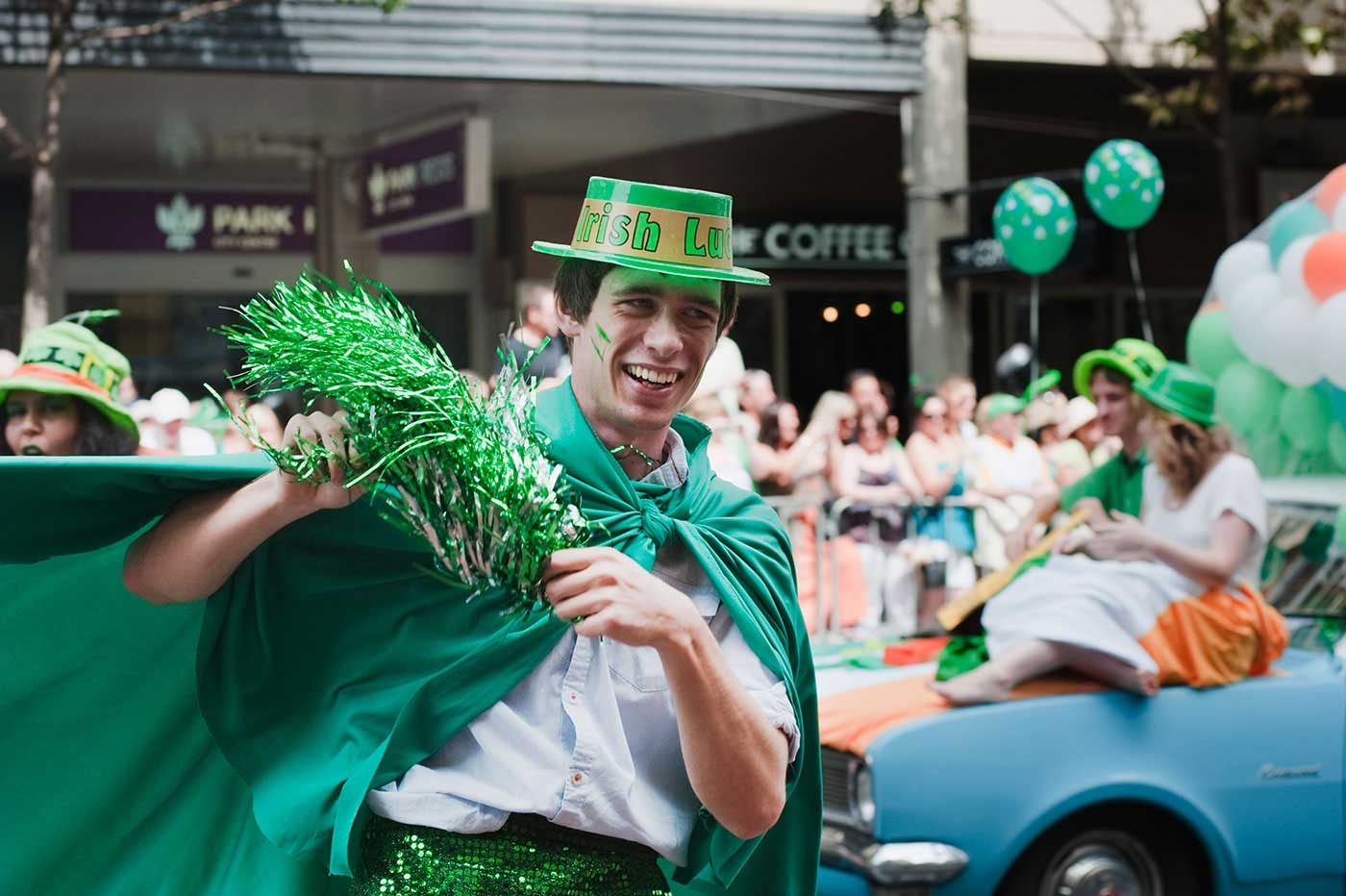 A man is wearing a green costume with a gimmick hat surrounded by other people wearing green in a procession on a city street. - click to view larger image