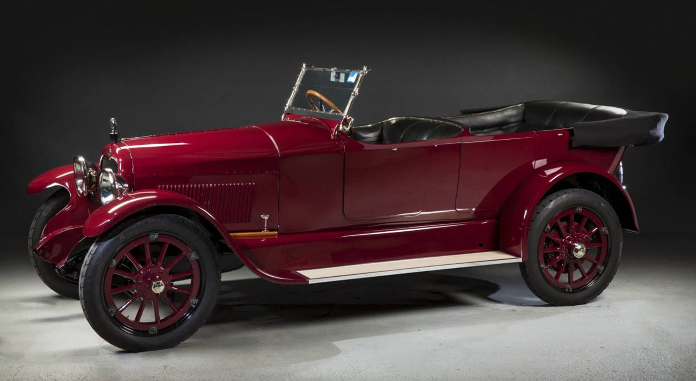 Side view of an open-topped, deep red automobile with black leather seats.  - click to view larger image
