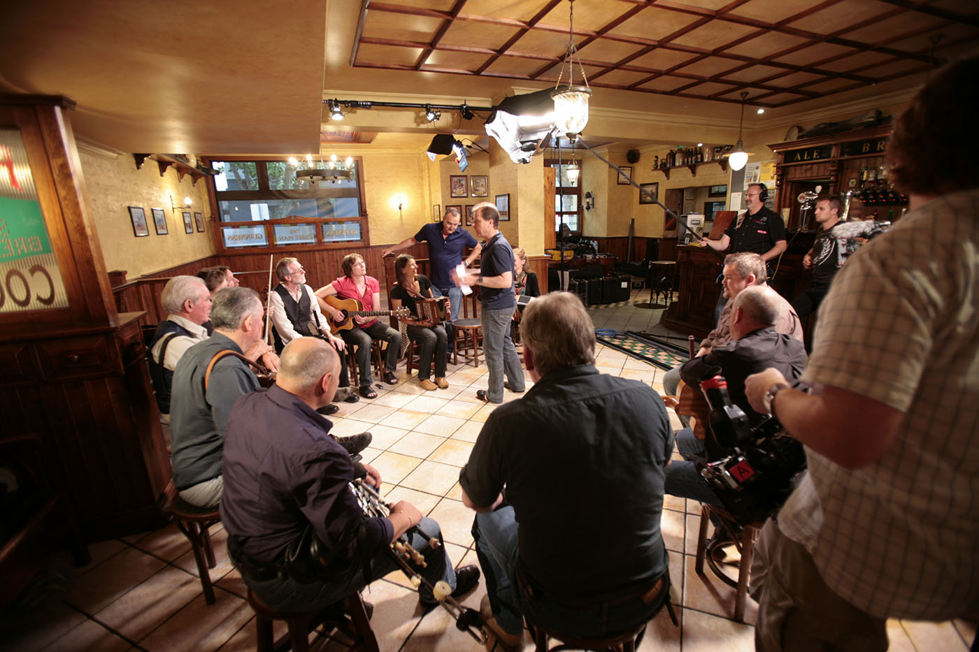 Musicians, Irish dancers and film crew on set in a pub. - click to view larger image