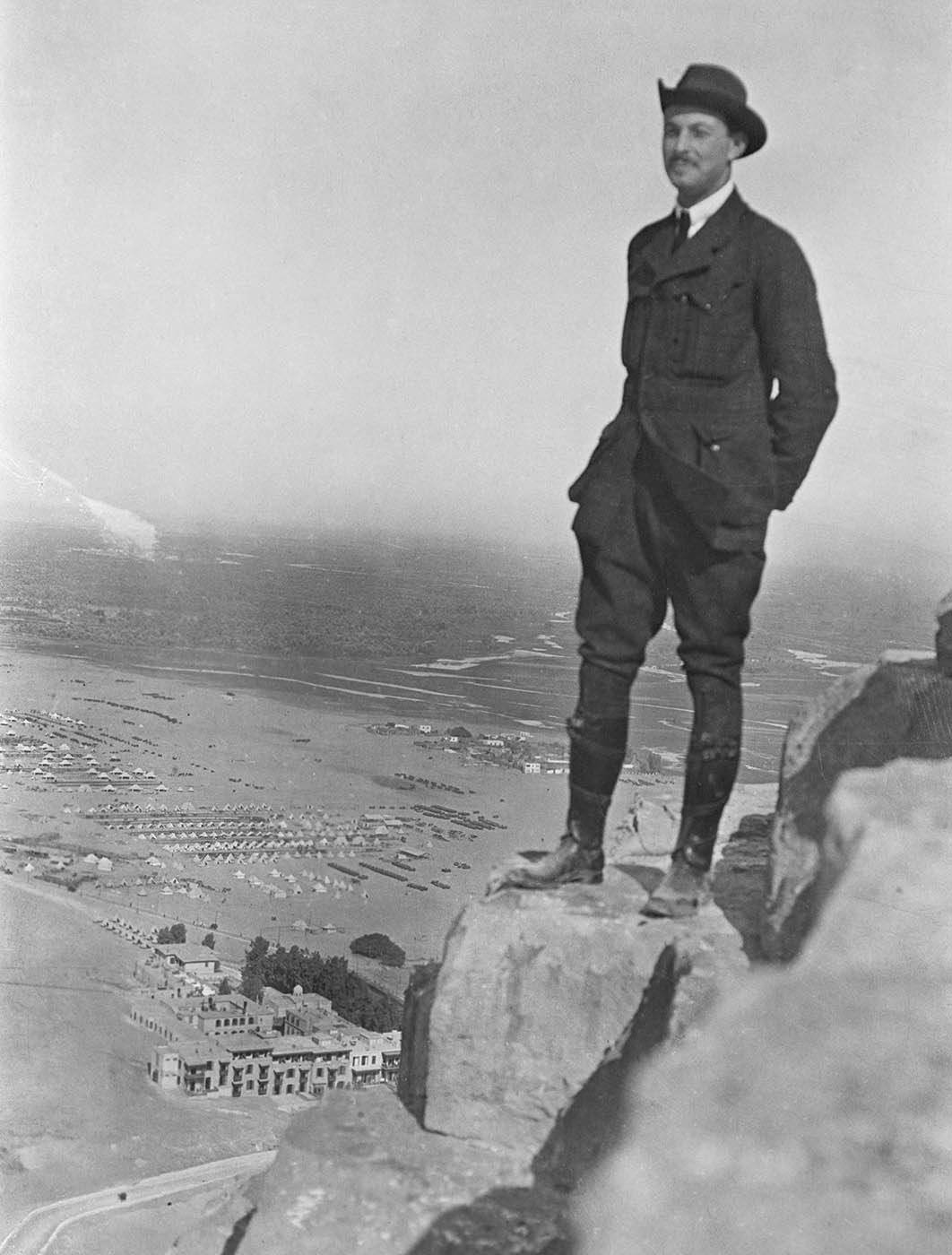 Portrait of a man standing on a rock overlooking buildings below. - click to view larger image