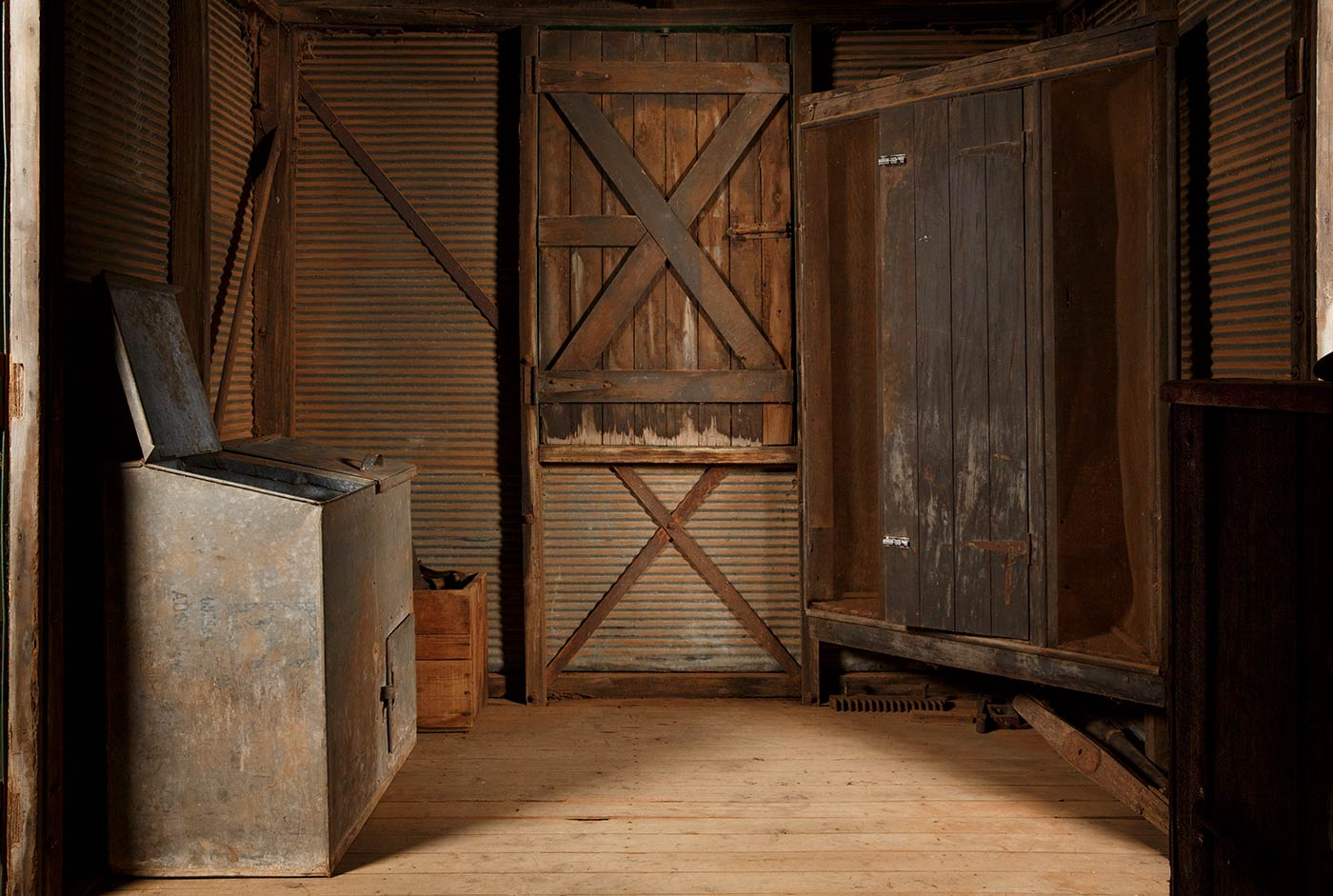 A cook's galley in the form of a metal-clad, timber and iron-framed box raised on wagon wheels. This view is of the rear of the galley with compartments on the left, the door in the centre and meat safe on the right. - click to view larger image