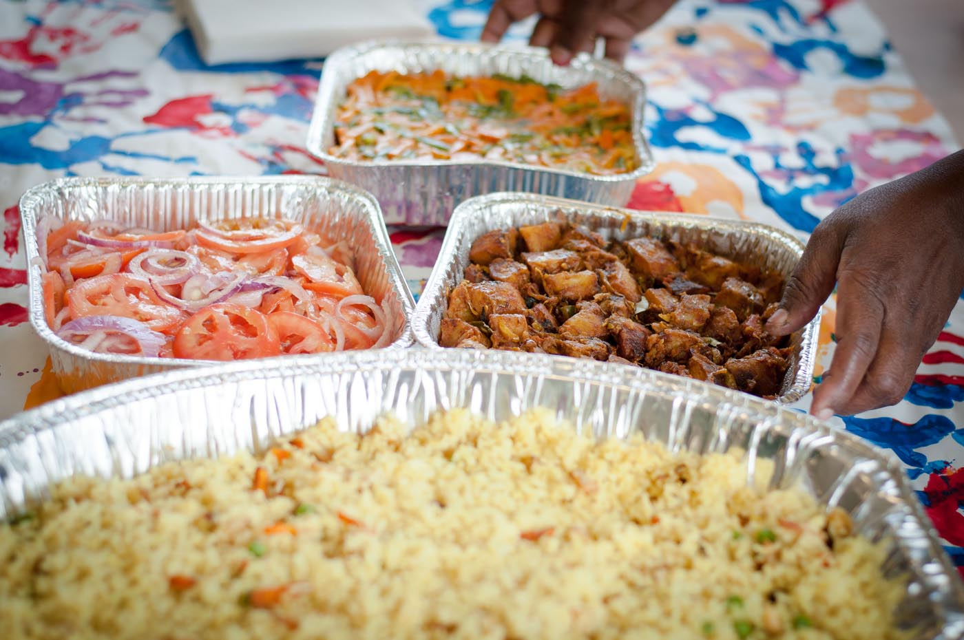 Photo showing four aluminium dishes containing various dishes including rice, tomatoes, meat and vegetables - click to view larger image