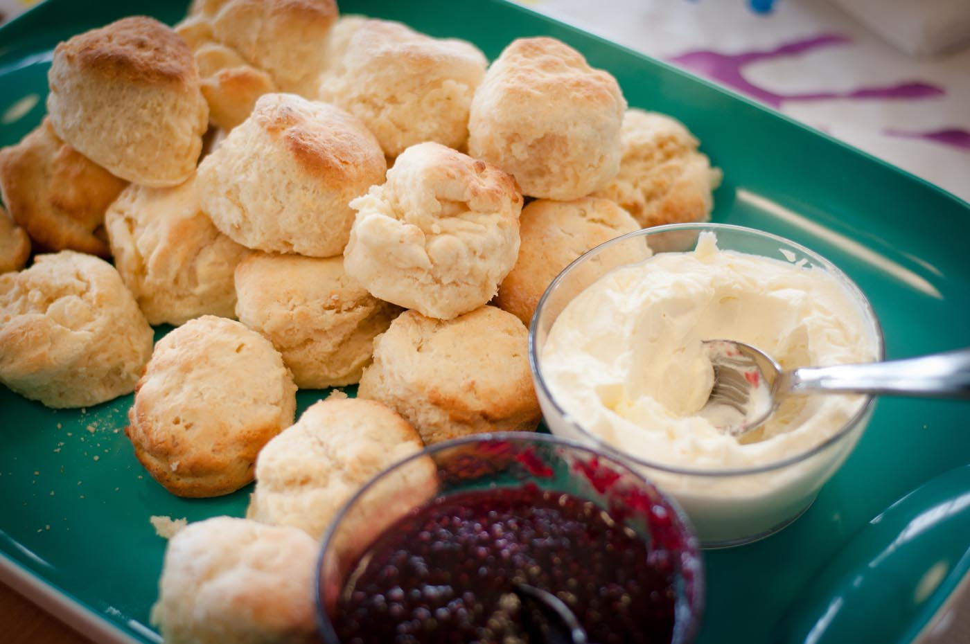 Photo showing a tray of scones with small bowls of jam and cream each with serving spoons in them - click to view larger image
