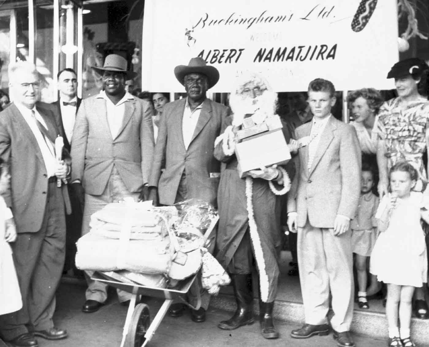 Black and white photo of Albert Namatjira with a group of townsfolk standing in front of a banner that reads: 'Buckinghams Ltd. ALBERT NAMATJIRA'. He is holding a wheelbarrow full of gifts and standing next to a man in a Santa Claus costume.