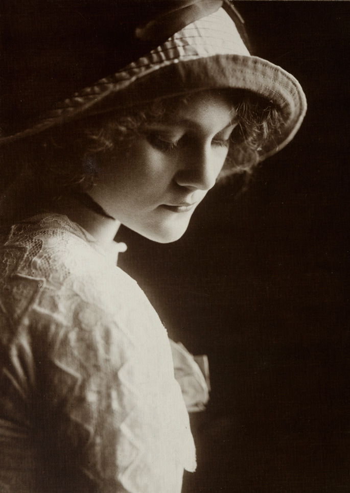Photograph of a woman gazing down to her right.