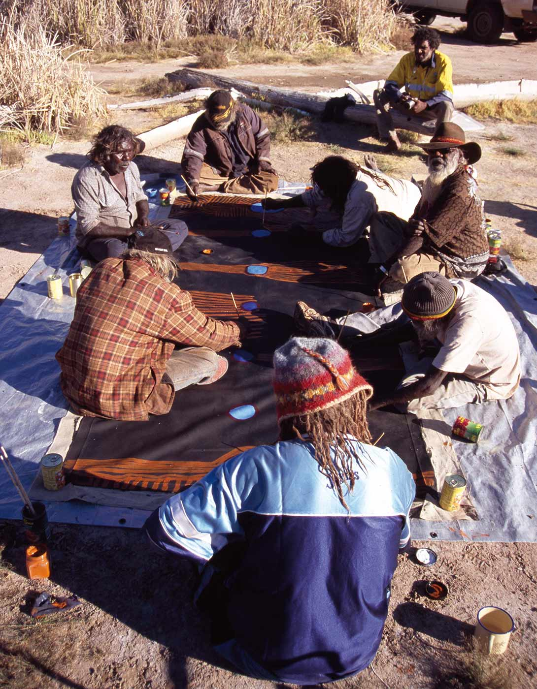 A group of men sitting on the ground collaborating in the painting of a large canvas.  - click to view larger image