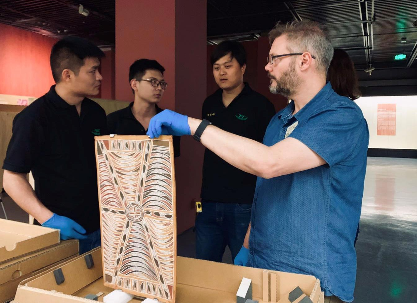 Four men inspect a bark painting in a gallery. - click to view larger image