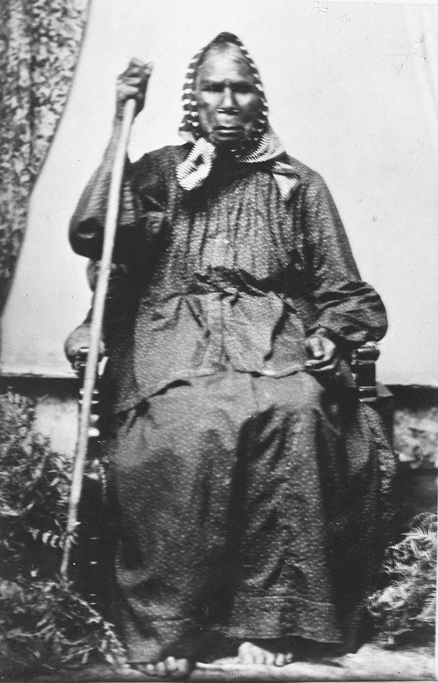 Black and white photograph of a seated elderly person holding a staff. - click to view larger image