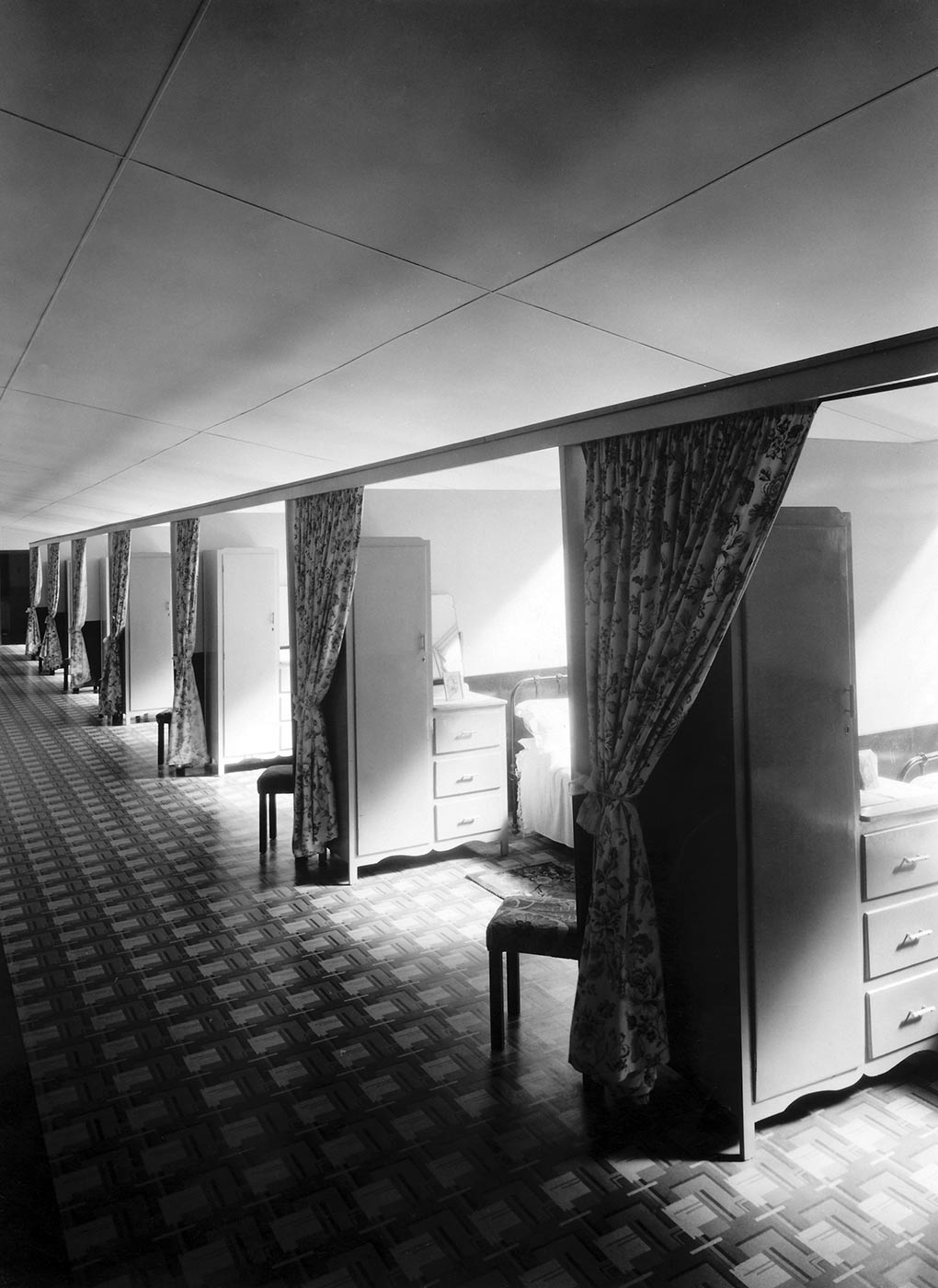 Black and white photograph showing a row of identical partitioned rooms. A high, narrow cupboard sits just inside each, with a chair sitting at an angle, under a curtain. A bedside table and bed is partially visible in the second partition from the front. - click to view larger image