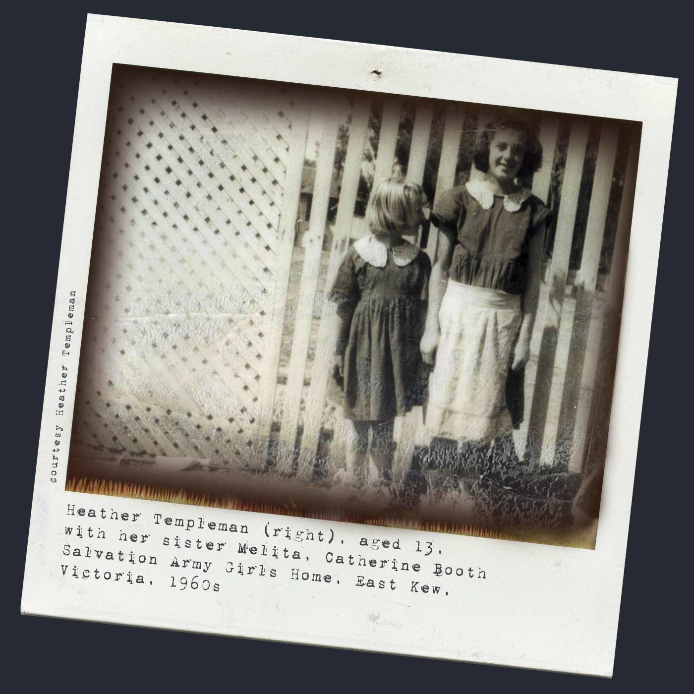 Polaroid photograph showing two girls standing in front of a white lattice fence. The smaller girl, on the left, turns her head to look at the older girl. Tyepwritten text below reads 'Heather Templeman (right), aged 13, with her sister Melita, Catherine Booth Salvation Army Girls Home, East Kew, Victoria, 1960s'. 'Courtesy Heather Templeman' is typed along the left side. - click to view larger image