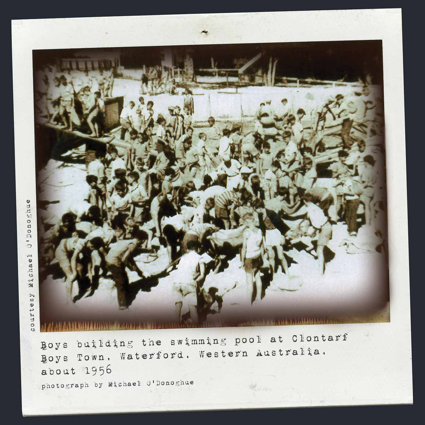 Polaroid photograph showing a large group of boys busy on a buliding site. Many dig in the foreground and others walk up a plank on the left. Typewritten text below reads 'Boys building the swimming pool at Clontarf Boys Town, Waterford, Western Australia, about 1956. Photograph by Michael O'Donoghue'. - click to view larger image