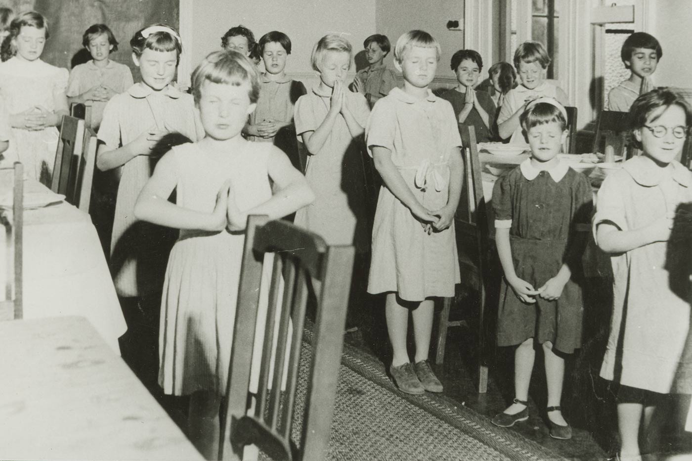 Black and white image showing a group of girls in a dining room, standing with hands together and eyes closed. - click to view larger image
