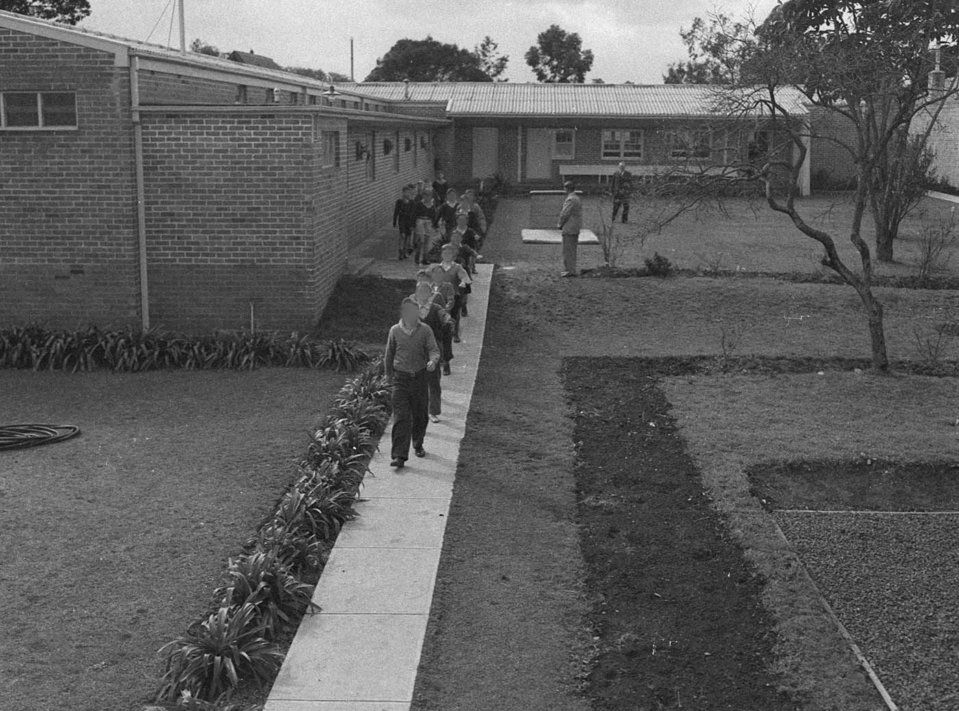Black and white photo showing a line of boys marching along a concrete path. Two men stand to the side watching the boys. - click to view larger image