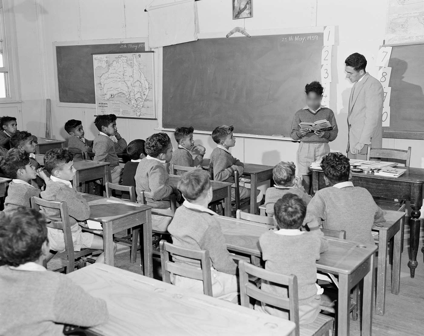 Black and white photo showing young Aboriginal boys in a classroom. One boy stands at the front, reading from a book, with the teacher standing beside him. A map of Australia hangs to the left of a blackboard. A boomerang sits above the blackboard. - click to view larger image