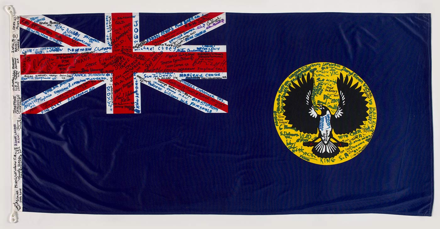 A colour photograph of the South Australian flag. Numerous signatures cover the Union Jack top left, and the state badge, a black and white bird on a yellow circle. More signatures appear along the white strip to the left of the flag. - click to view larger image