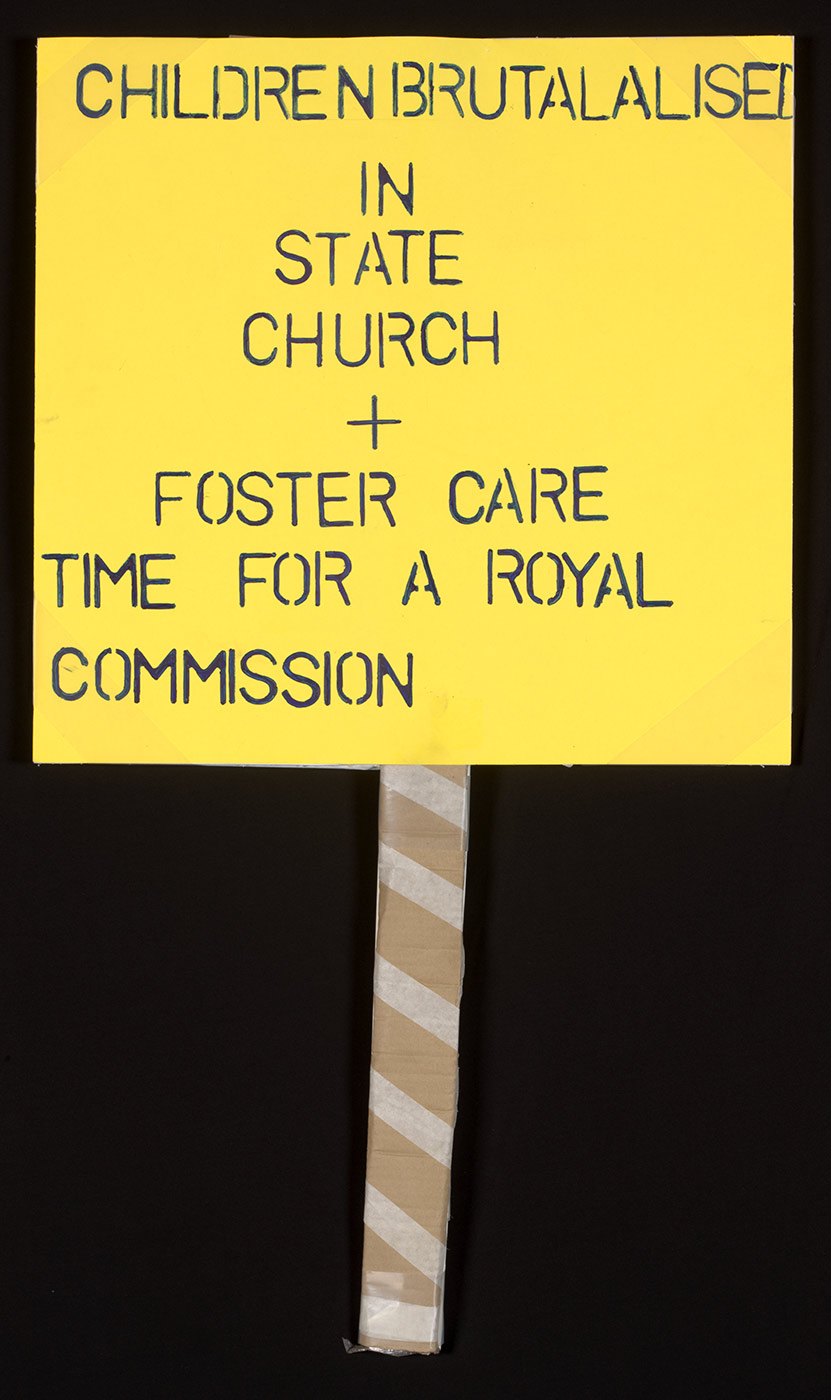 A photograph of a yellow protest placard with the words in capital letters, 'CHILDREN BRUTALALISED (sic) IN STATE CHURCH + FOSTER CARE TIME FOR A ROYAL COMMISSION'. The post is brown with what appears to be white tape wrapped around it. - click to view larger image