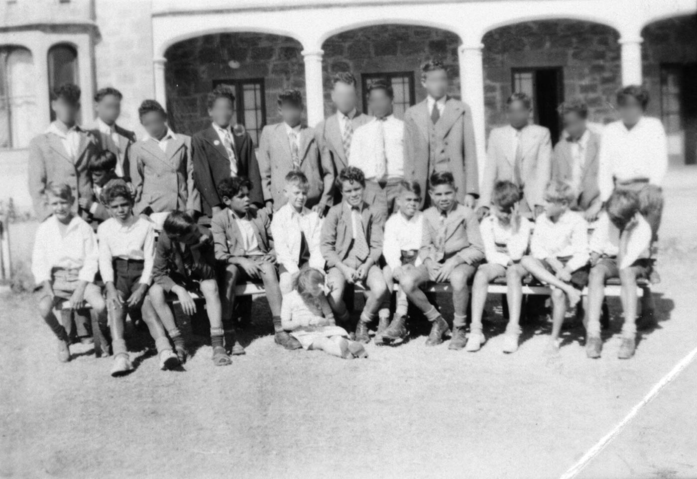 Black and white image showing two rows of boys, one sitting and one standing. Some of the boys' faces have been blurred. - click to view larger image