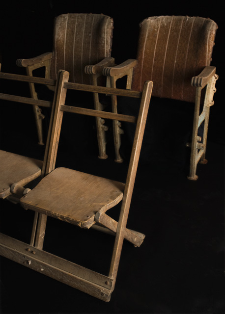 Two rows of conjoined theatre seating. Two plain wooden chairs stand at the front. Two plusher upholstered chairs at the back. - click to view larger image