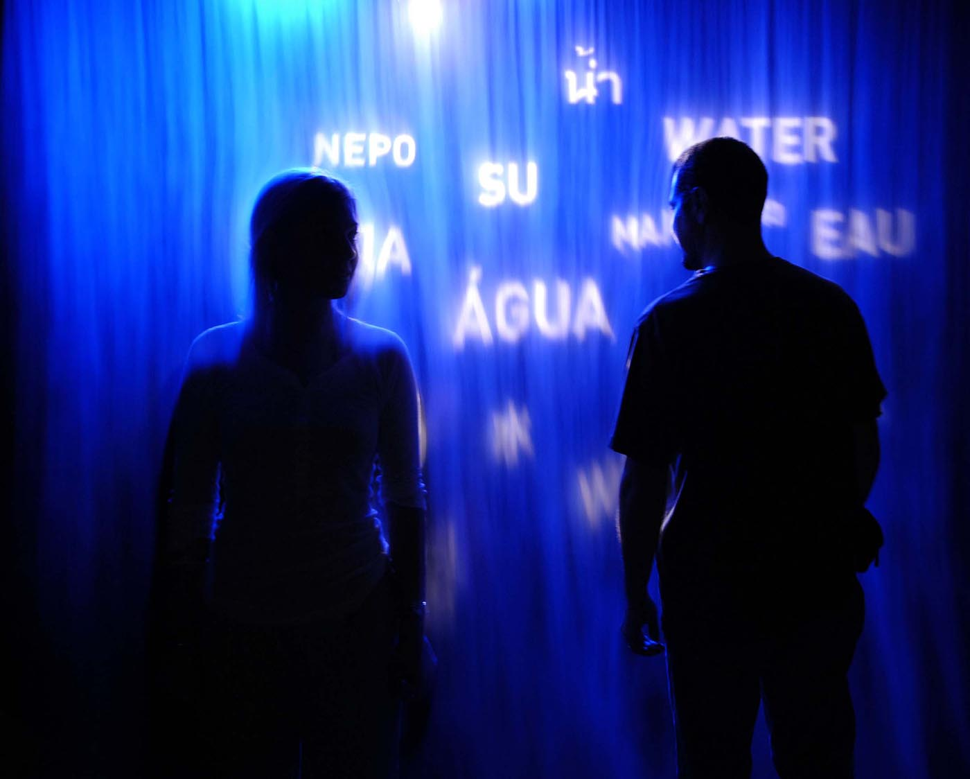 A man and woman shown in silhouette, standing in front of a blue rippled screen, with the words 'NEPO', 'SU', 'AGUA', 'EAU', 'WATER' and other partially visible text in white.