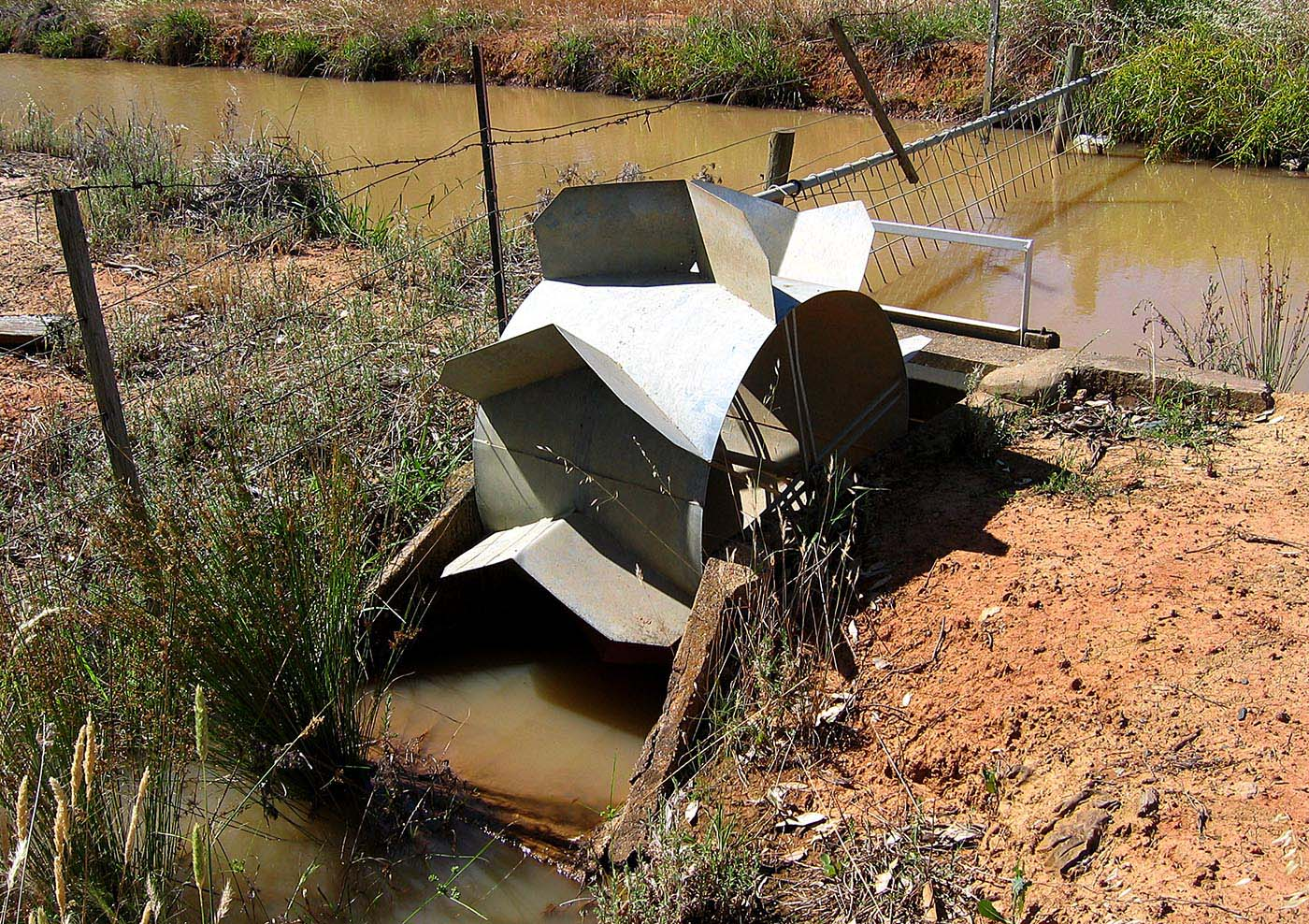 Metal wheel mounted in concrete casement beside an irrigation channel.