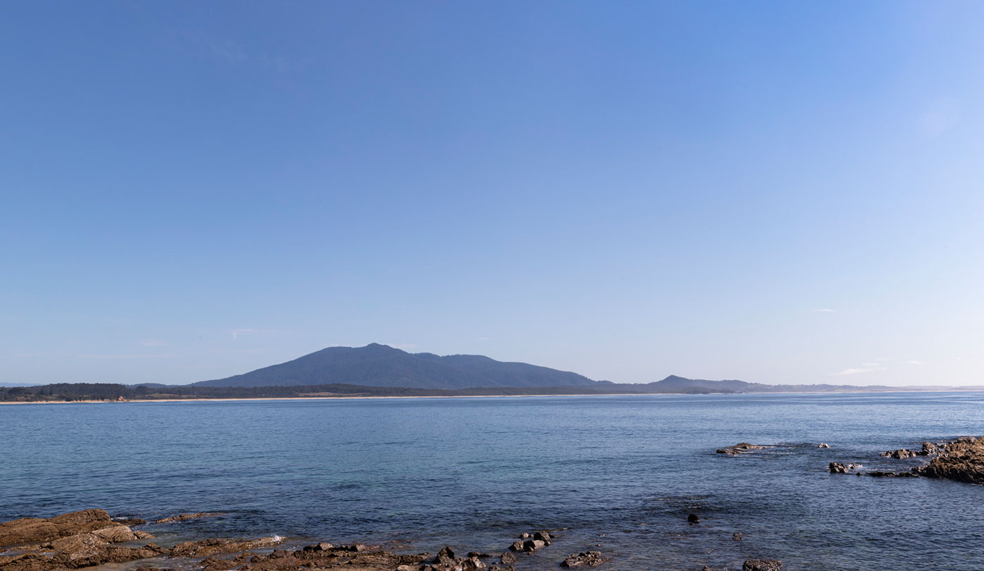 Colour photo of a bay with rocks in the foreground and a beach and mountain in the background.