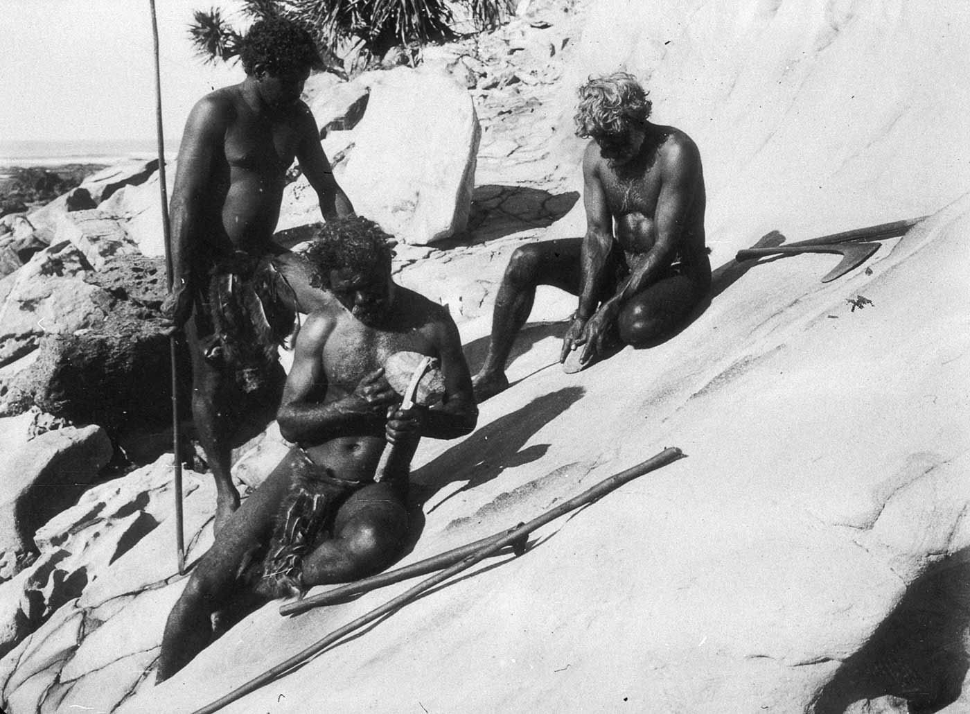 Black and white photograph of three men positioned on a rocky slope, making stone tools. - click to view larger image