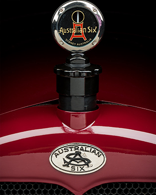 View of a polished red motor car bonnet and badge that reads 'Australian Six'.