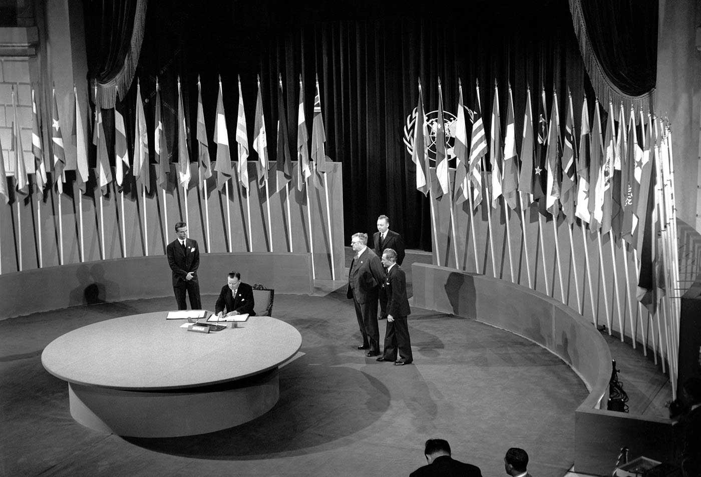 Interior black and white photo of man sitting at large round table signing a document, with four men standing behind him and a series of flags arranged behind them. - click to view larger image
