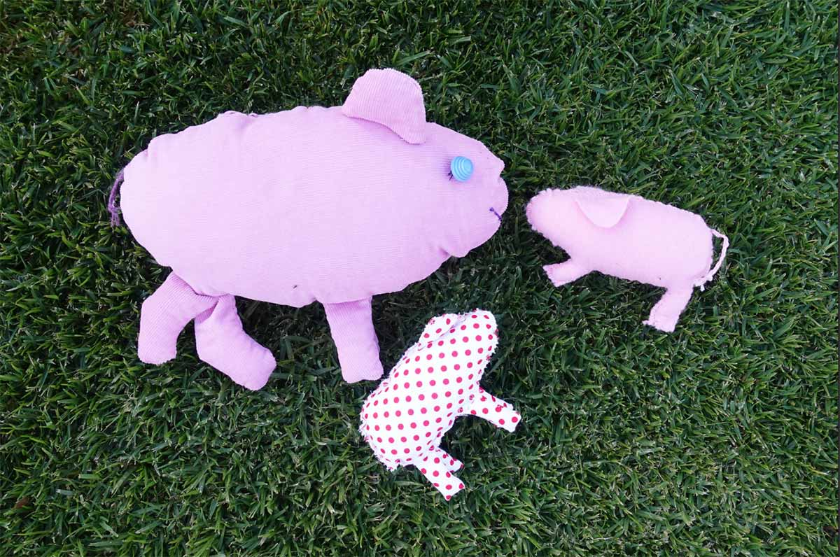 A display of three hand made pigs.