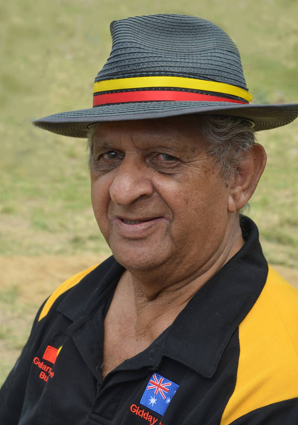 Portrait of an elderly man wearing a Fedora hat with a yellow and red stripe. - click to view larger image