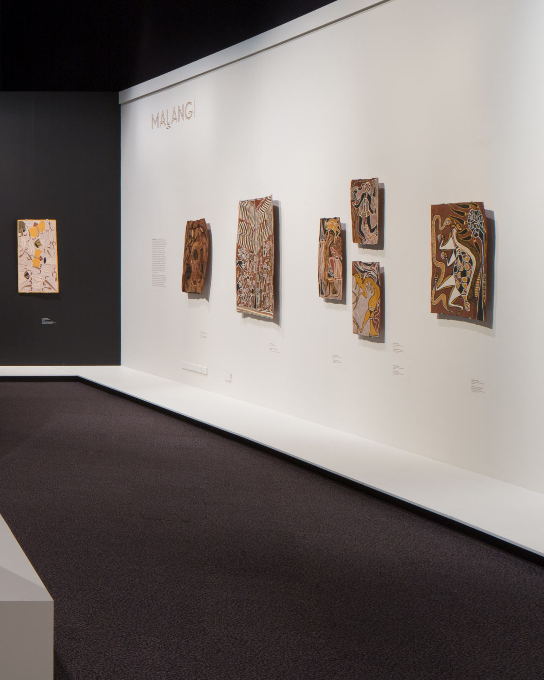 Exhibition space featuring bark paintings mounted on walls.