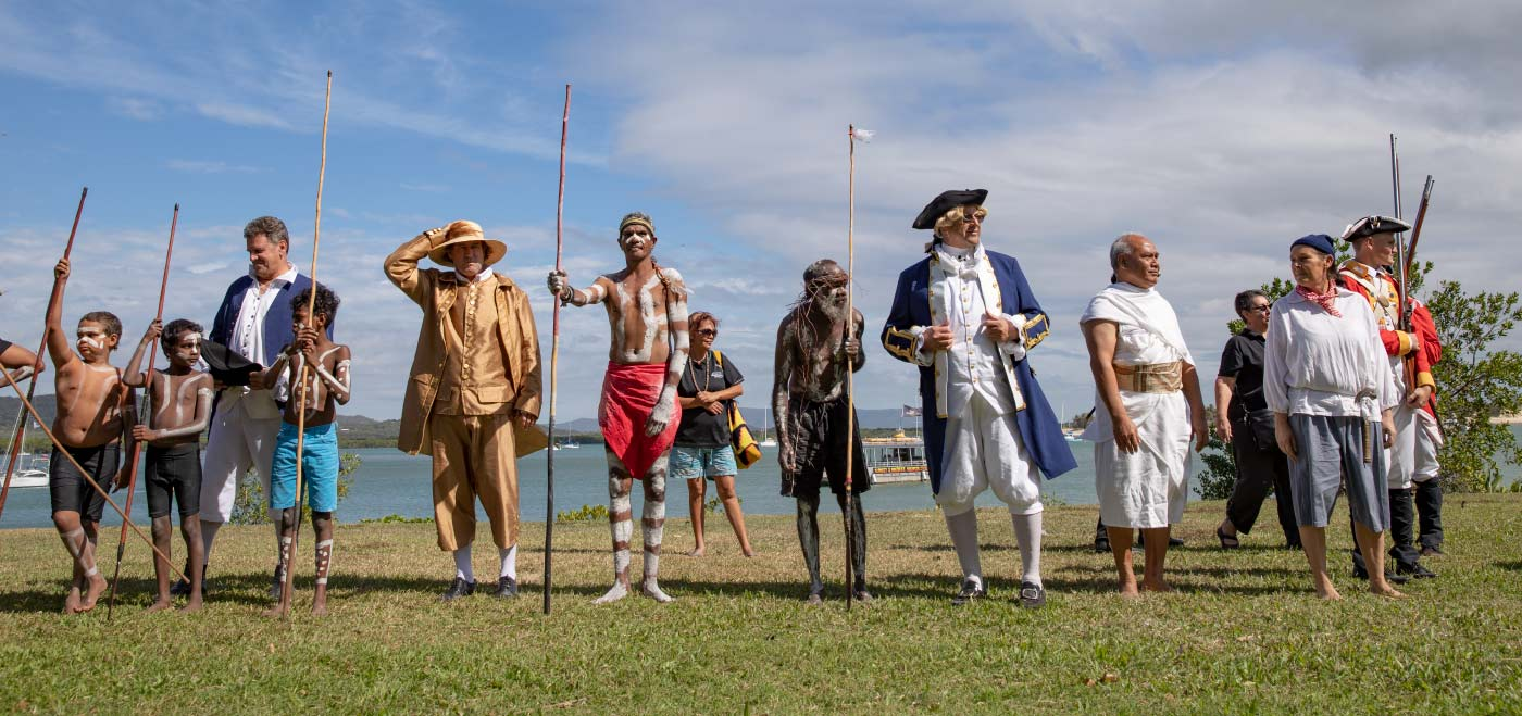 Colour photo of a group of people in costume acting out a scene as part of an outdoor festival. - click to view larger image