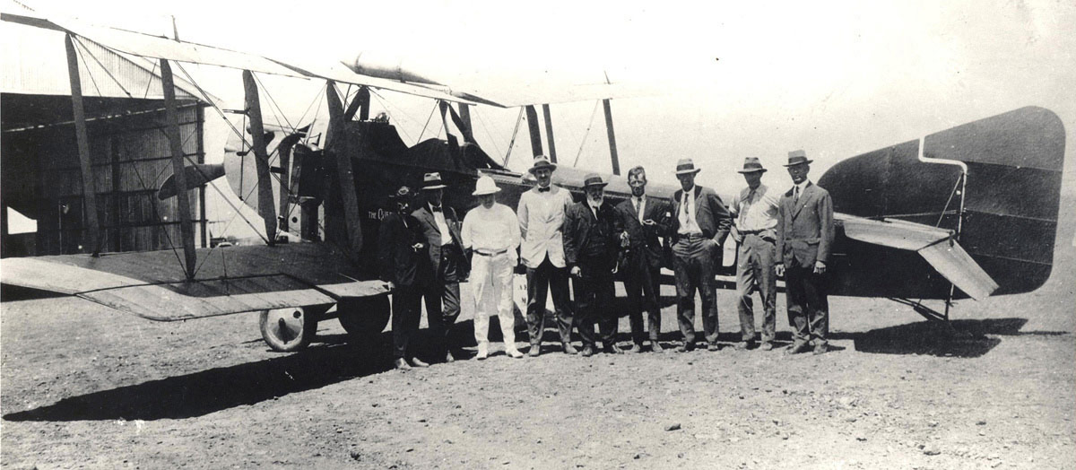 Biplane with nine men standing, posing for the camera, by its fuselage.