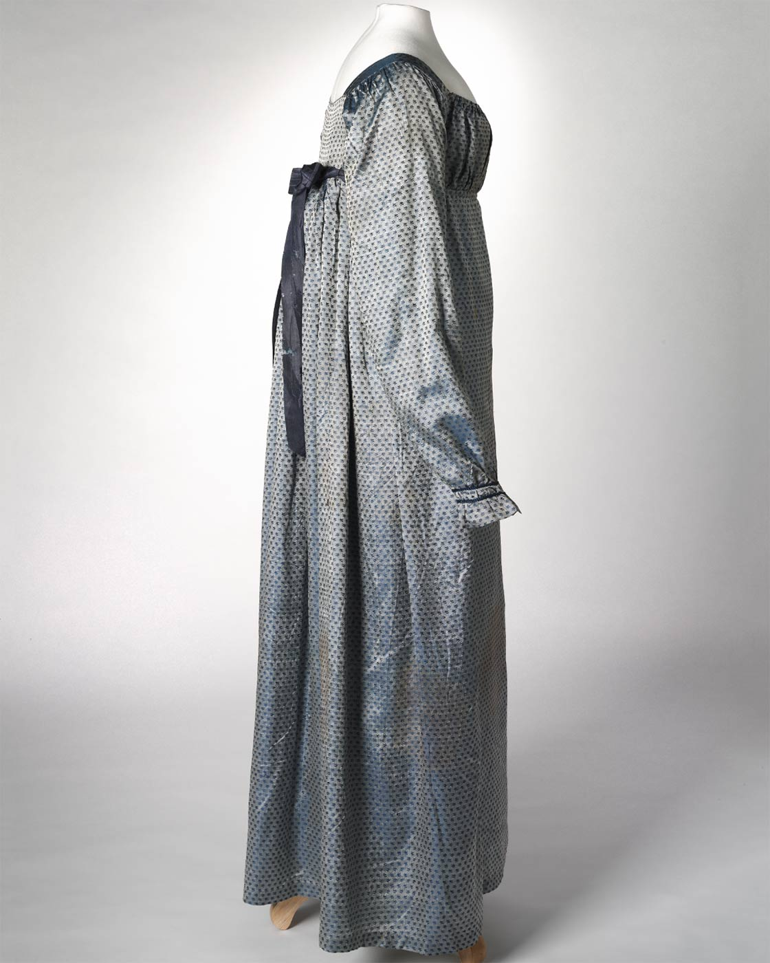 Side view of a blue silk full length empire-line dress. - click to view larger image