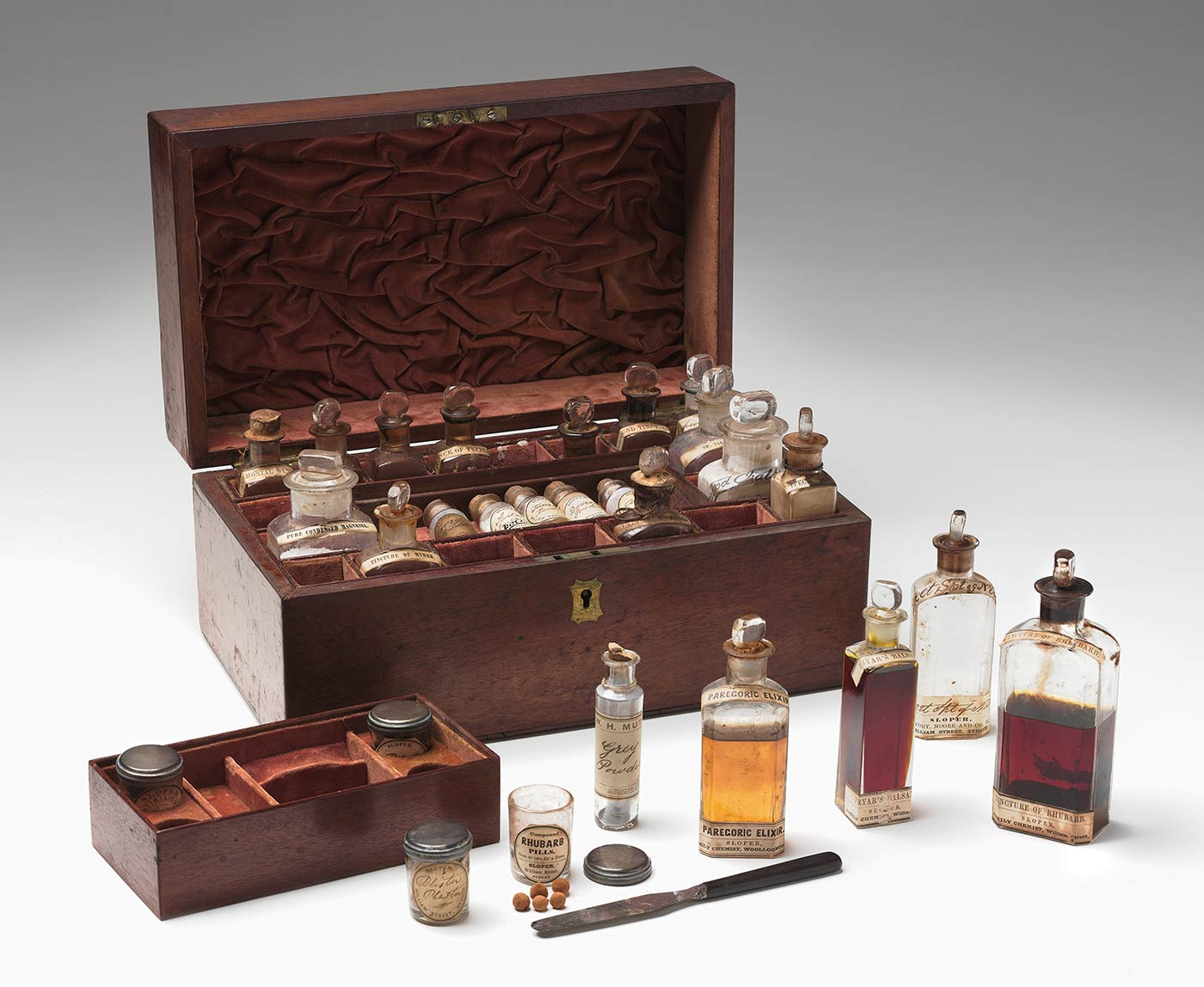 Wooden medicine chest with hinged lid. The interior is lined in red velvet with compartments around the edge and one central compartment holding two trays that lift out. The chest contains 27 bottles and jars holding medicinal substances and a small knife.