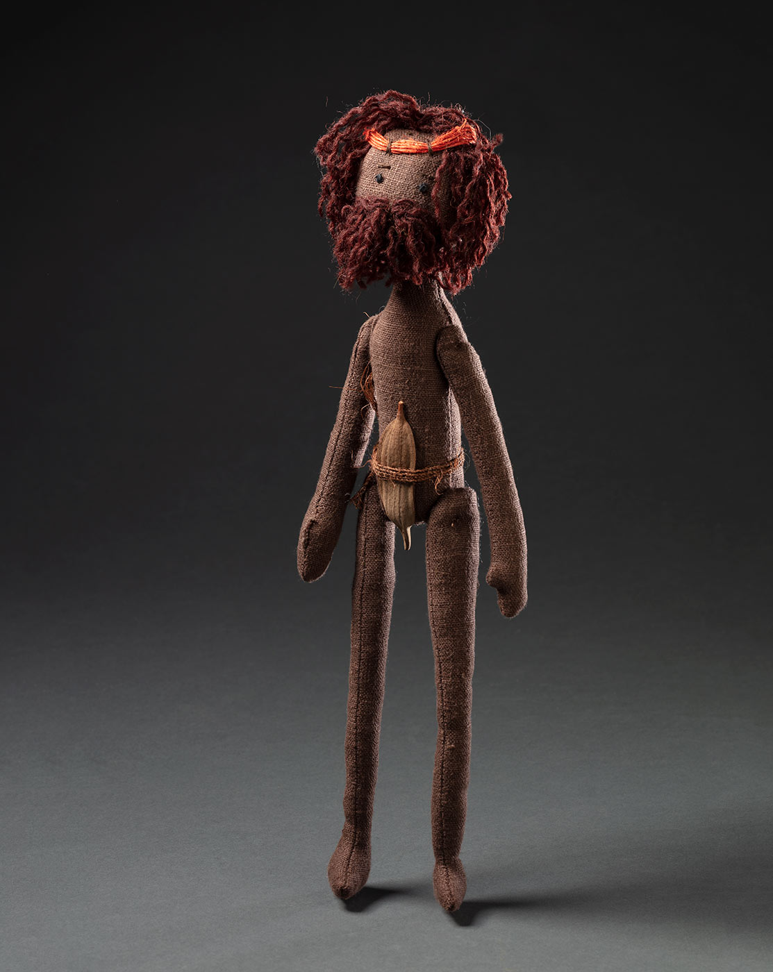 A soft sculpture based on ancestor creator spirit Toonku, a male figure. He has a cloth body, wearing a belt and leaf around waist and a brown wool beard. He also has a red string headband around his brown wool hair on his head and has stitched black eyes. - click to view larger image