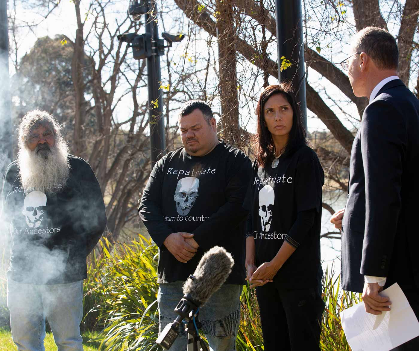 Photo of four people standing in the garden surrounded by smoke and media equipment.