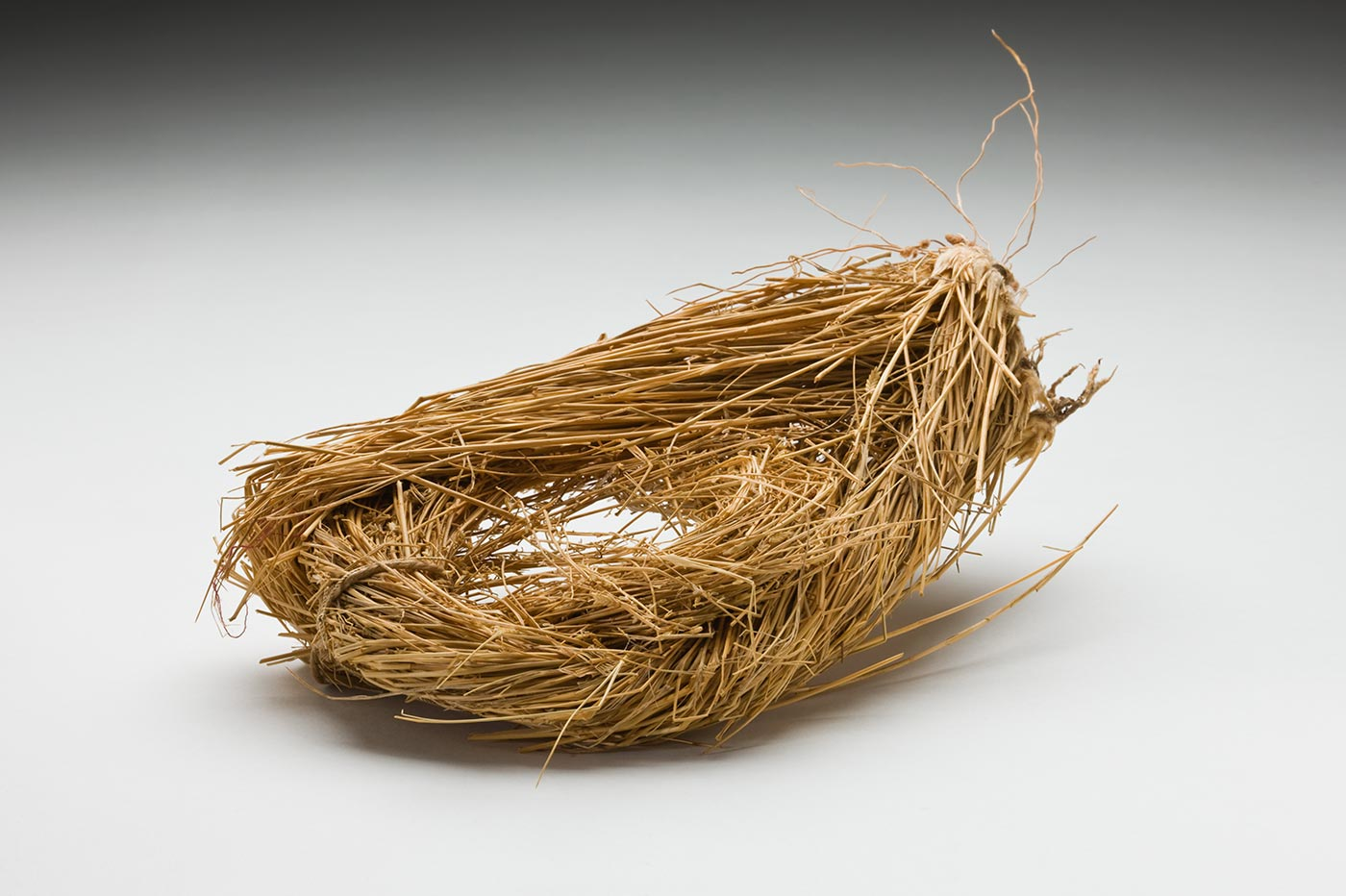 An undyed grass tear drop like shaped head pad. Two bunches of grass have been twisted and folded over to form the tear drop like shape. The narrow end includes the grass roots. Two tags are attached with string. - click to view larger image