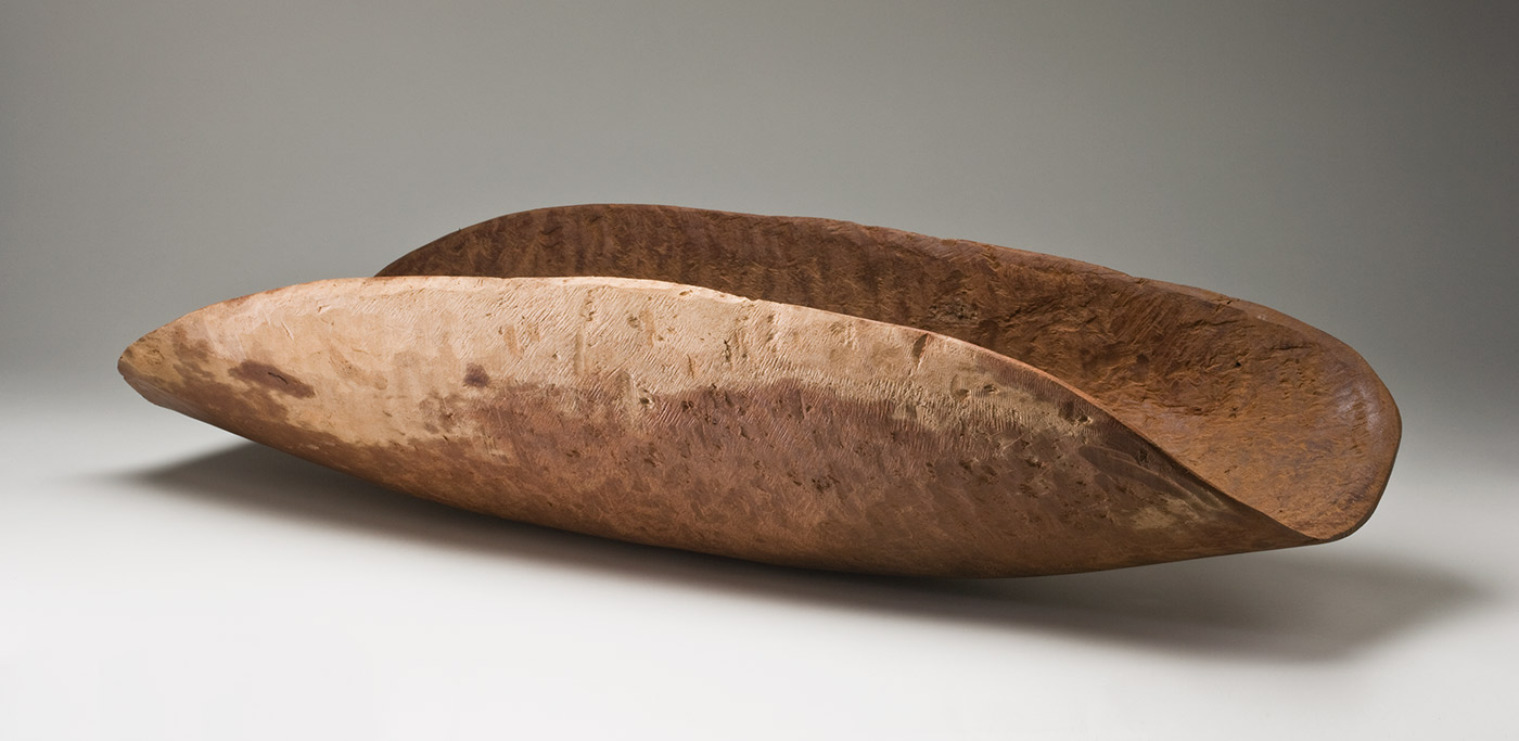 A large red-brown wooden concave oval container with drill holes in the surface and a pale patch of wood along one edge. The inner surface is rough and shows tool marks as well as drill holes with adhesive and sawdust around them. The outer surface is smoothed but shows the wavy grain of the wood. - click to view larger image