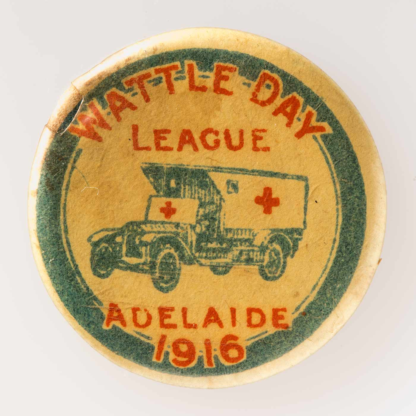 Circular Wattle Day badge, depicting ambulance in blue & white with red crosses on it, white background, blue border. Inscriptions: 'WATTLE DAY / LEAGUE' (in red above ambulance); 'ADELAIDE / 1916' (in red below ambulance). Plastic coated. - click to view larger image