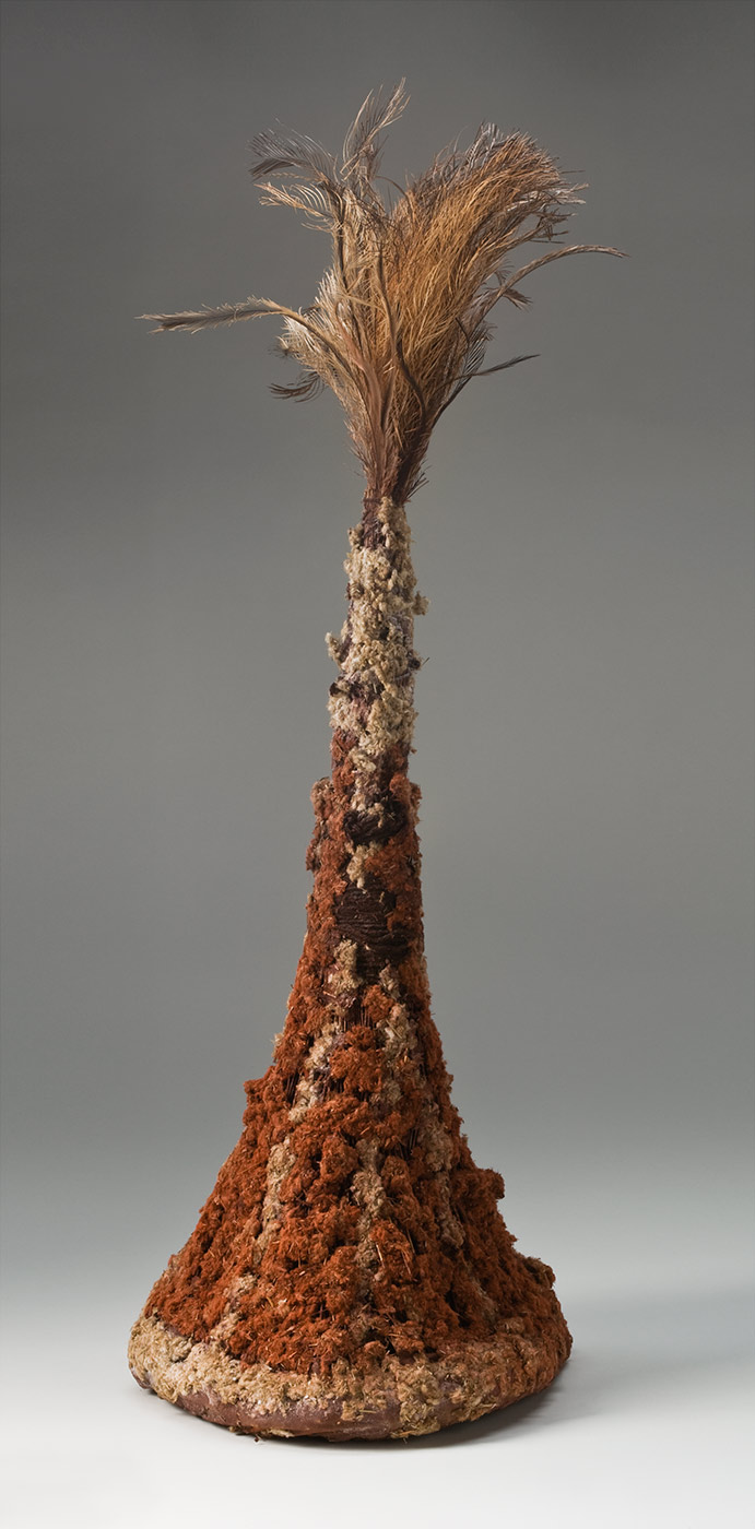 A tall conical headdress made of plant fibres attached to a firm circular ring at the base and covered with pigmented fluffy plant fibre with feathers at the top. The ring at the base is pigmented red and the plant fibre stalks are attached around it. The fibres are bunched together towards the top and wrapped with maroon coloured string. The plant stalks are covered with fluffy plant fibre which is decorated with red pigment in vertical stripes on the bottom half and cream at the top. At the top of the headdress is a bunch of fluffy and spiky brown, tan and grey feathers. - click to view larger image