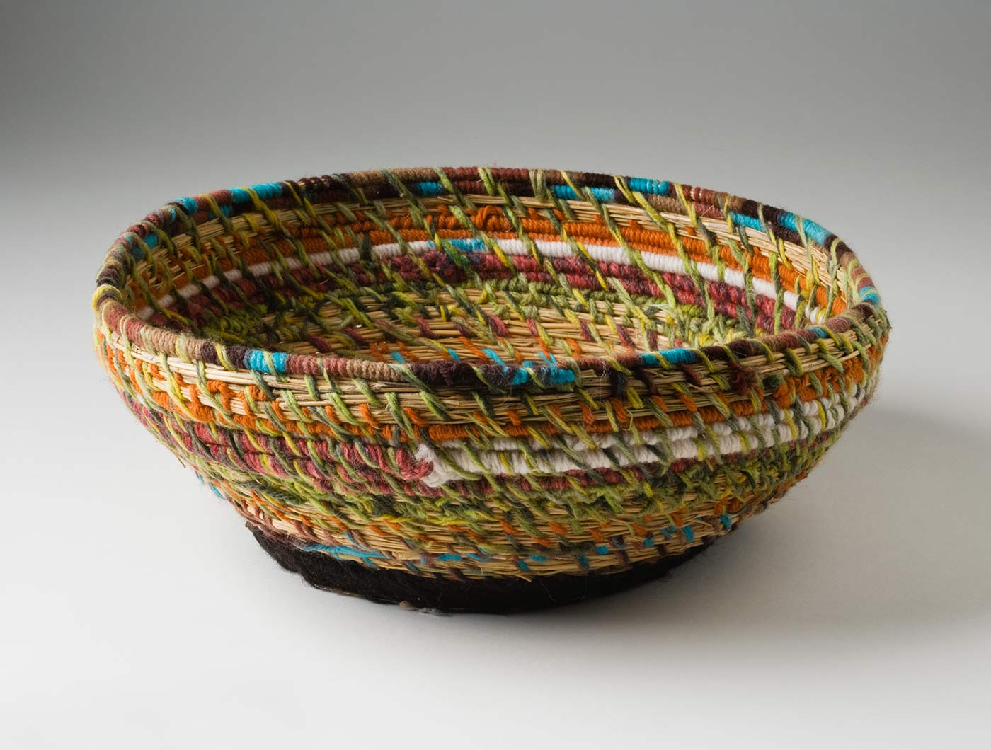 A circular coiled yarn and plant fibre basket with a flat metal base. The base is made of a blue 'Fray Bento / Steak and Kidney Pie' tin lid which has been attached to the yarn section with black yarn through holes punched in the metal. The coiled yarn in muted tones of green, orange, yellow,pink, turquoise, white and orange, is spaced out so the plant fibre centre can be seen. - click to view larger image