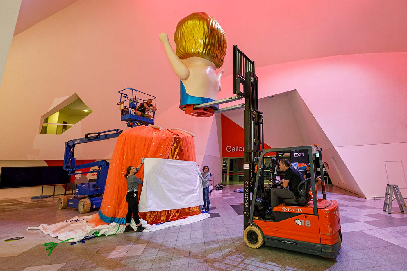 Colour photograph of staff installing a giant kewpie doll in a large hall. - click to view larger image