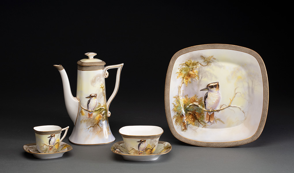 A ceramic tea set of two cups and saucers, a tea pot and square plate. All are hand-painted with an image of a kookaburra in a wattle tree.  - click to view larger image