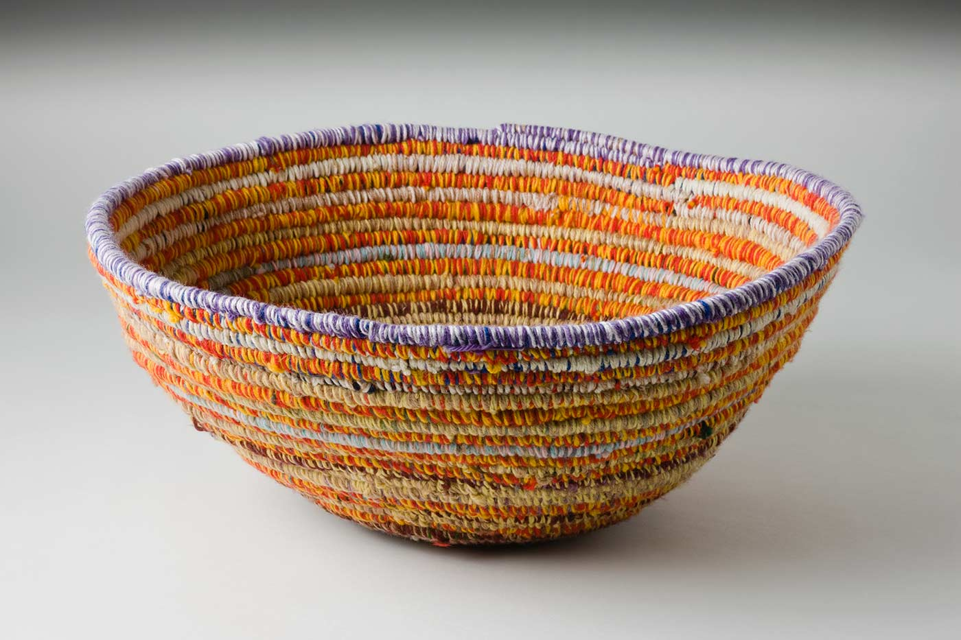 A circular coiled multicoloured yarn and plant fibre basket. The plant fibre in the very centre of the basket is covered with orange-green yarn, followed by horizontal alternate yarn coverings over the fibre. The alternate yarn colours are brown, brown-blue, yellow-blue, yellow-brown, tan-cream, tan-brown, cream-pink, red-yellow, yellow-tan, light blue-light pink with various combinations of red, yellow, tan and white up to the top coil. The top plant fibre coil is covered by white-purple yarn. - click to view larger image