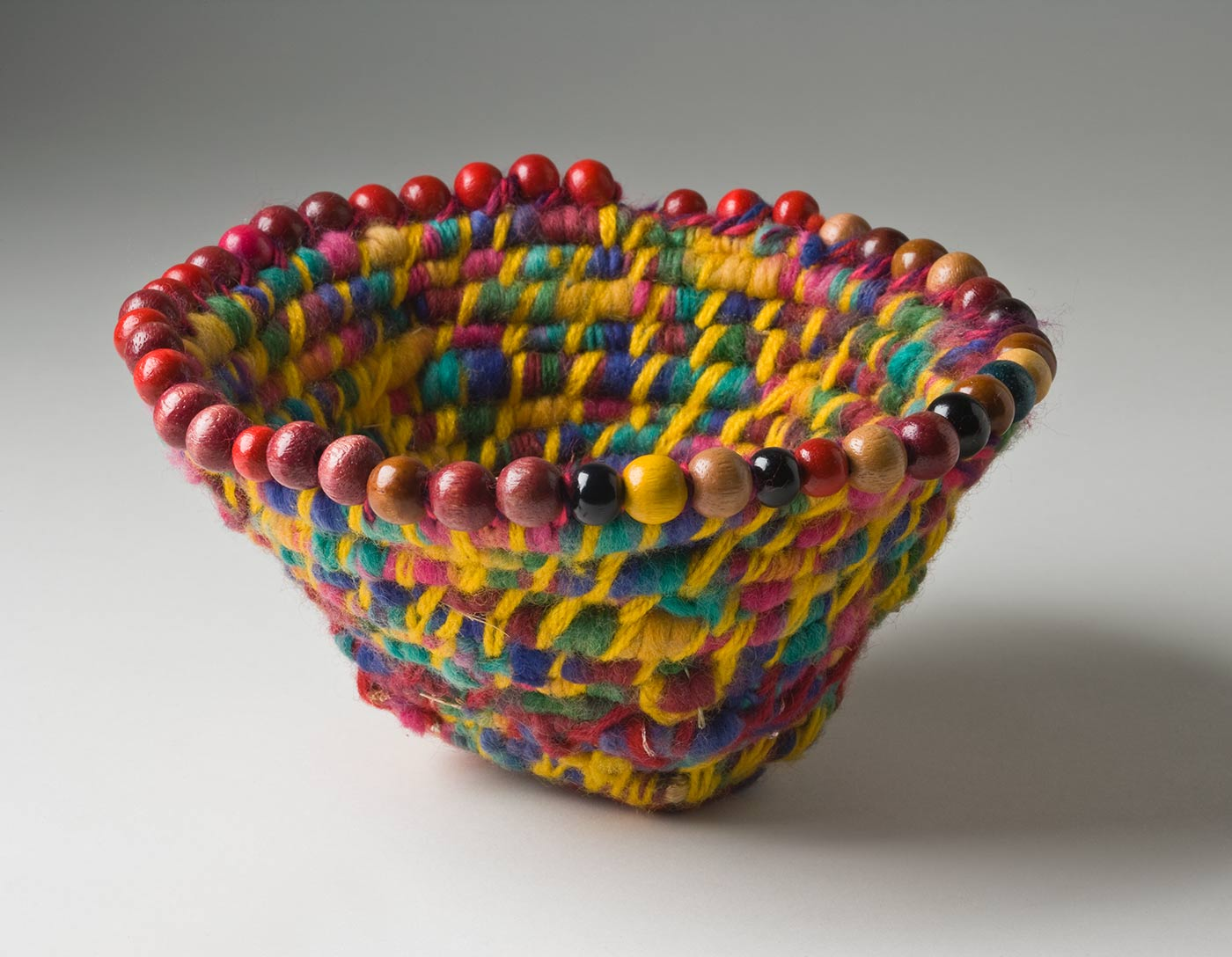 A funnel shaped basket of multicoloured coiled yarn over plant fibre with a beaded edge. The yarn is rainbow coloured with a dominant yellow tone. The maroon yarn used at the base has small silver sequins in it. The round wood beads attached at the top edge of the basket are mostly red and brown with a few green, yellow, black and natural coloured ones. - click to view larger image